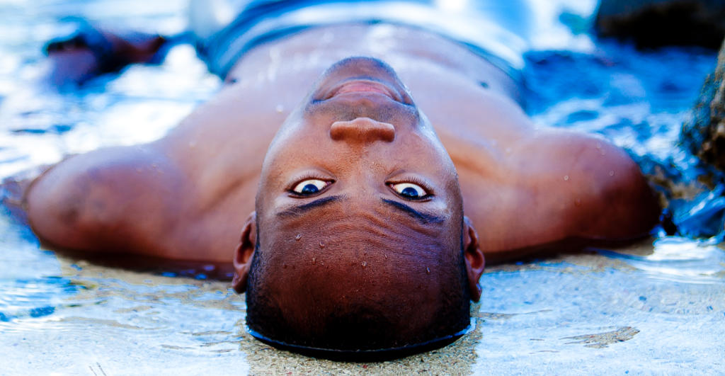 Samuel Sagor lying in the water on the beach in Mauritius