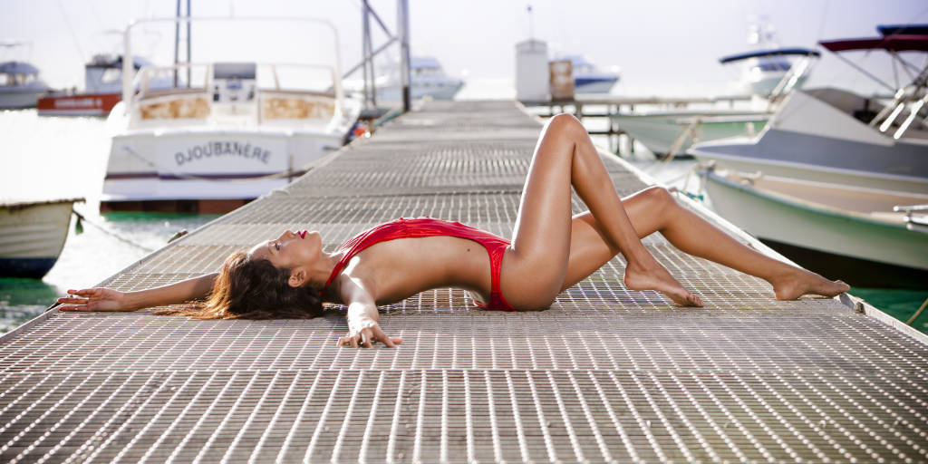 Woman in red swimsuit lying across a jetty in front of boats