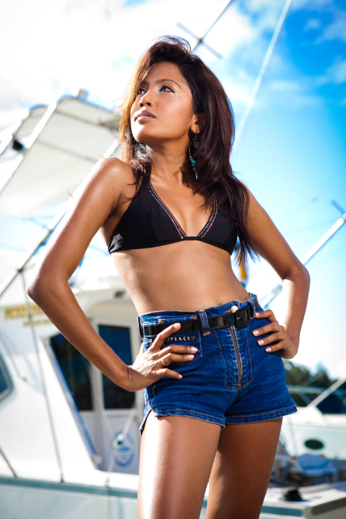 portrait of a woman in black bikini and blue denim shorts in front of fishing boats