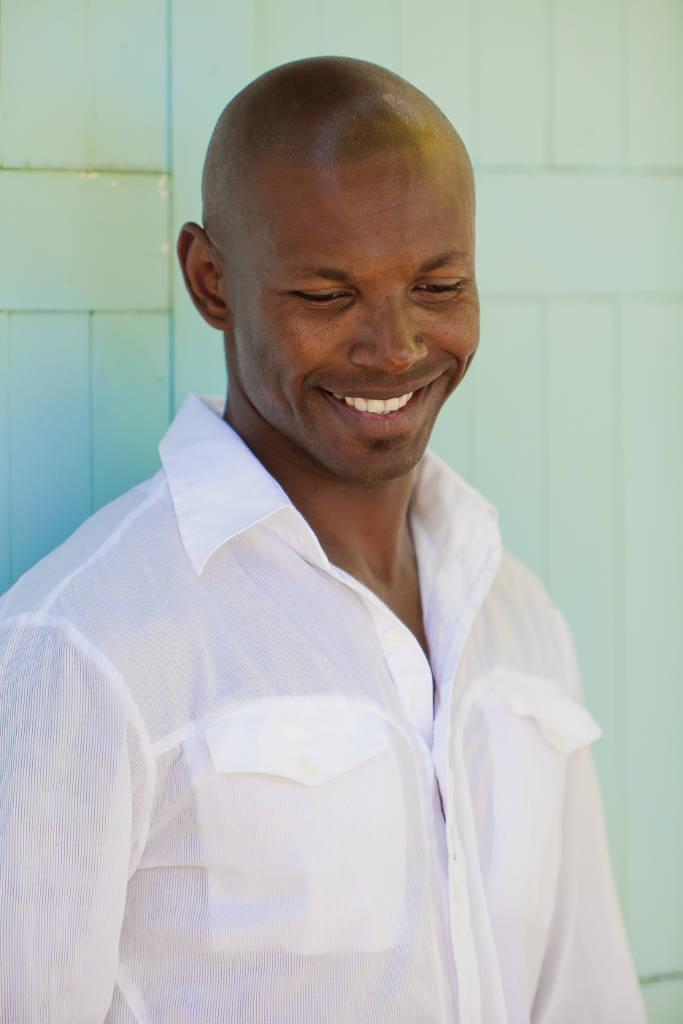 smiling Steve Bontemps model in Mauritius against turquoise shutters