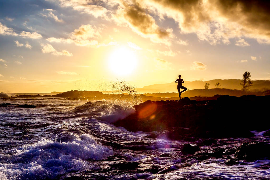 vriksasana yoga on the beach at sunset